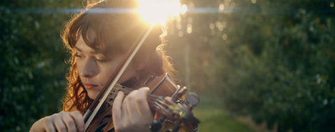 Photo of  female violinist playing in between a line of trees with the sun behind her.