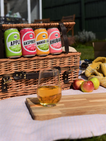 Photo of 4 cans and one glass of Pulp cider, and  picnic basket on a sunny day.
