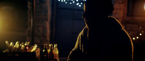 Photo of Joe sat almost in silhouette with fairy lights behind him and cider bottles in the background.