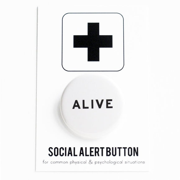 Round pinback button that says ALIVE. Black text on a white background.  The button is pinned to a Social Alert Button backing card.