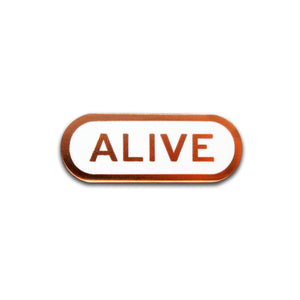 Capsule shaped enamel pin that says ALIVE.  Copper text and outline on a white enamel background