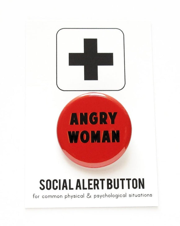 Round pinback button that says ANGRY WOMAN. Black text on a red background. Button is pinned to a Social Alert Button backing card