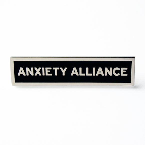 Rectangle Enamel Pin that says ANXIETY ALLIANCE.  Silver text and outline on black enamel background