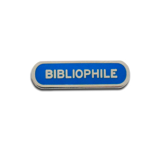 Capsule shaped enamel pin that says BIBLIOPHILE.  Silver text and outline on a royal blue enamel background.