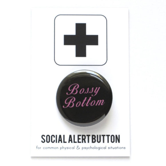 Round pinback button that says BOSSY BOTTOM. Pink text on a black background.