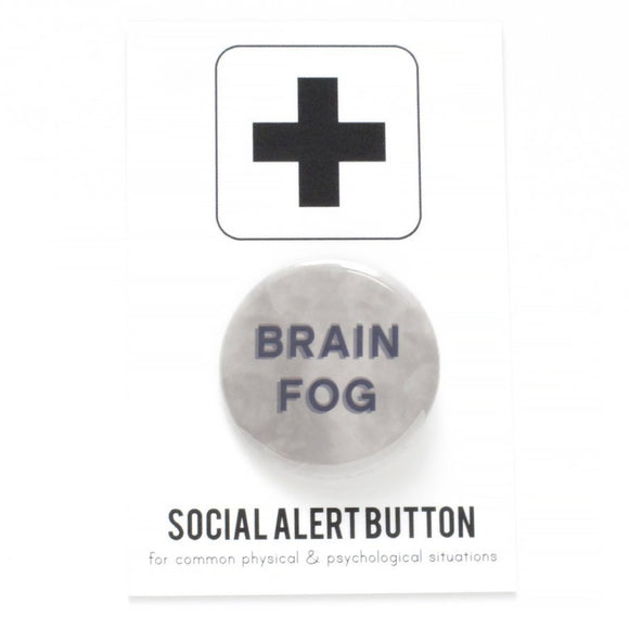 Round pinback button that says BRAIN FOG. Purple-gray text on a cloudy grey  background