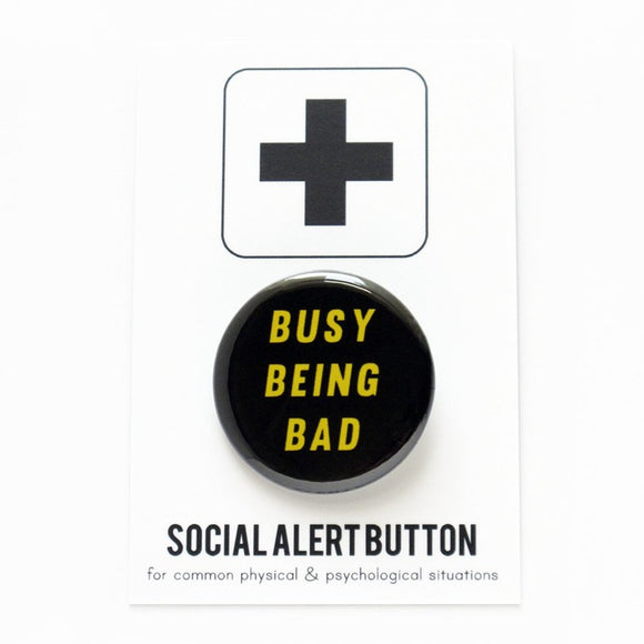 Round pinback button that says BUSY BEING BAD. Yellow text on a black background.