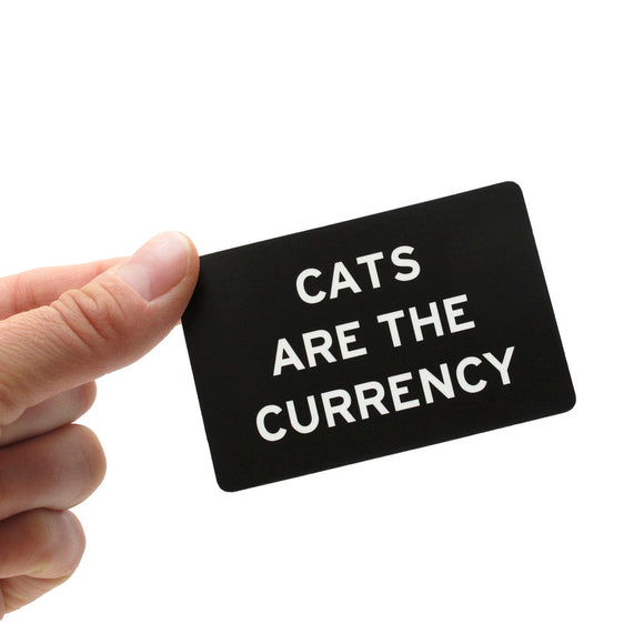 Rectangle sticker that says CATS ARE THE CURRENCY.  White text on a black background.