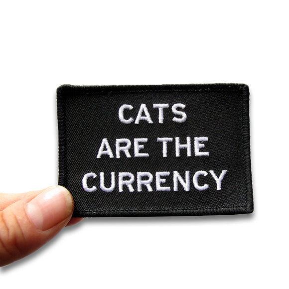 Rectangle patch that says CATS ARE THE CURRENCY.  White text on a black background.