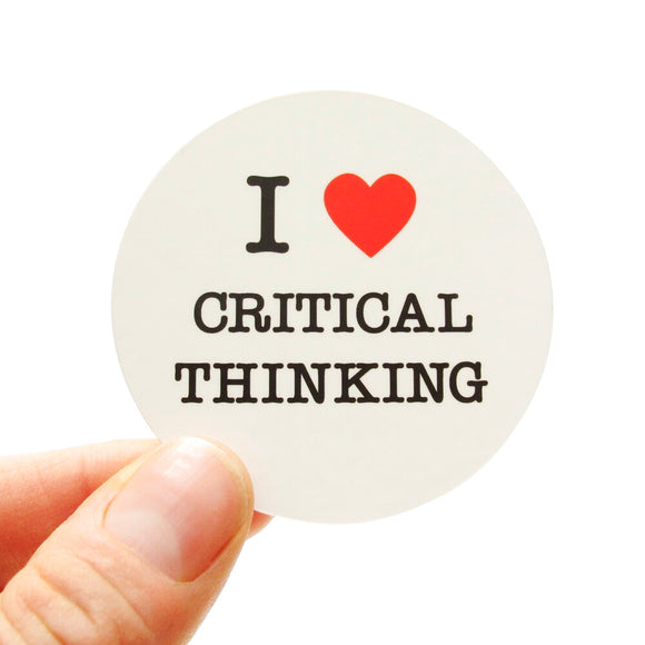 Round die-cut sticker that says I LOVE CRITICAL THINKING. The text is black with a red heart signifies the word love. The background is white.