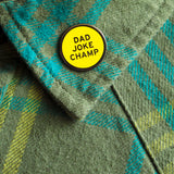 Round enamel pin the says DAD JOKE CHAMP on the lapel of a forrest green plaid flannel shirt