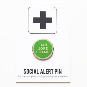 Round enamel pin the says DAD JOKE CHAMP.  In three different color choices.  Gunmetal text and outline with a yellow enamel background. Gunmetal text and outline with an orange enamel background. And silver text and outline on a green enamel background.