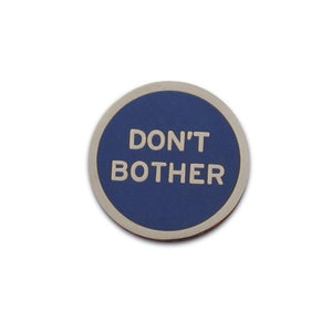 Round enamel pin that says DON'T BOTHER.  Silver text and outline on a navy blue background
