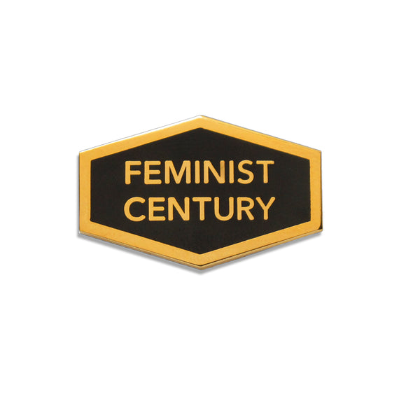 Hexagon shaped hard enamel lapel pin that says FEMINIST CENTURY.  Gold text and outline on a black background.