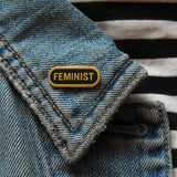 Capsule shaped enamel pin that says FEMINIST on the lapel of a blue denim jacket.