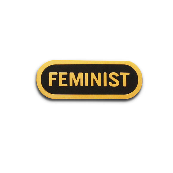 Capsule shaped enamel pin that says FEMINIST.  Gold text and outline on a black enamel background
