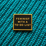 Rectangle enamel pin that says FEMINIST WITH A TO-DO LIST on a teal knitted sweater.