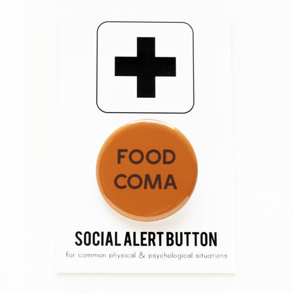 Round pinback button that says FOOD COMA.  Brown text on a reddish orange background.