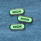 Three capsule shaped enamel pins that say HIGH on a blue denim background.