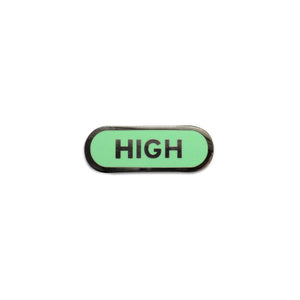 Capsule shaped enamel pin that says HIGH.  Silver text and outline on a mint green enamel background.