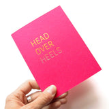 Hand holding a magenta Valentine's Day greeting card that says Head Over Heels