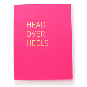 Magenta greeting card with gold, hot foil pressed text, that says HEAD OVER HEELS