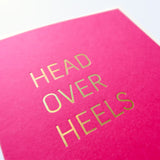 Magenta greeting card that says HEAD OVER HEELS.  Close up of the gold hot foil pressed text.
