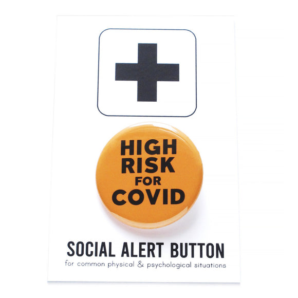 Round pinback button that says HIGH RISK FOR COVID.  Button is neon orange with black text. The button is on a black and white Social Alert Button backing card with a black plus sign at the top.