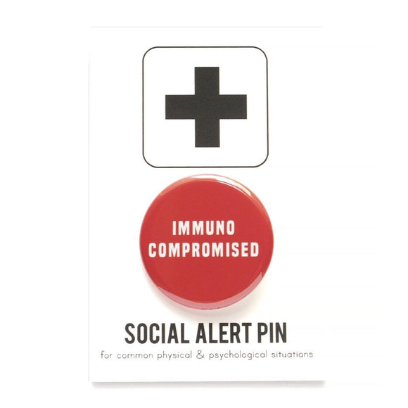Round pinback button that says IMMUNOCOMPROMISED. White text on a red background.  Affixed to a Social Alert Pin backing card.