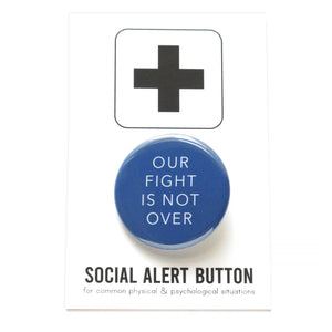 Round pinback button that says OUR FIGHT IS NOT OVER. White text on a royal blue background. Button is pinned to a Social Alert Button backing card