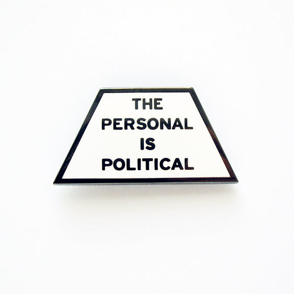 Trapezoid shaped pin that says THE PERSONAL IS POLITICAL. Gunmetal silver text  on a white enamel background.