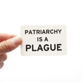 Rectangle sticker that says PATRIARCHY IS A PLAGUE.  Black text on a white background.