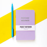 Lavender pocket notebook that says PSYCHIC WOUNDS in silver text, next to a pen for size reference.  The height of the notebook is about the same as the pen.