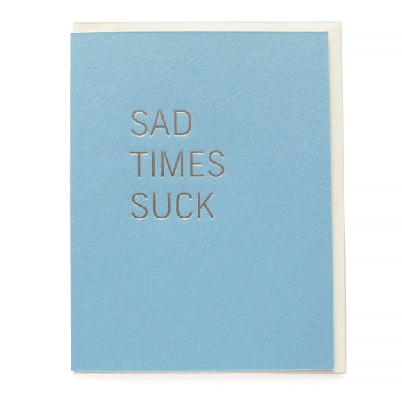 Powder blue greeting card that says SAD TIMES SUCK in silver hot foil pressed text.