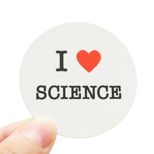 Round die-cut sticker that says I LOVE SCIENCE. The text is black with a red heart signifies the word love. The background is white.