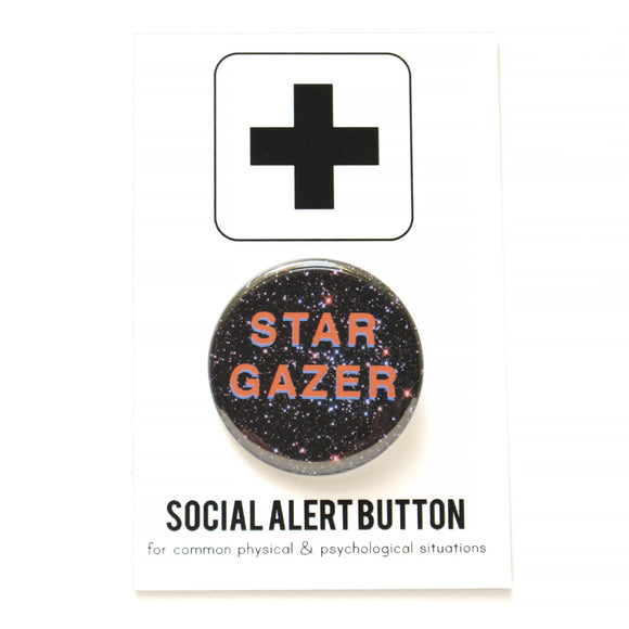Round pinback button that says STAR GAZER.  Salmon pink text with a light purple drop shadow, set on a background of the night sky.  The button is pinned to a Social Alert Button backing card.