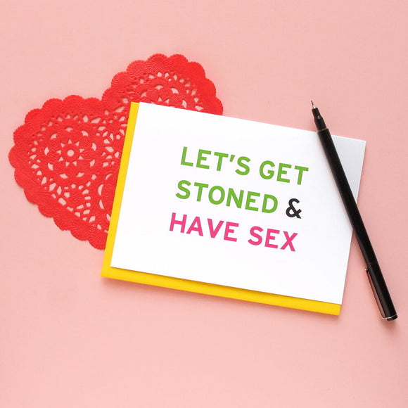 Light pink background with red paper lace heart, and a greeting card that says Let's Get Stoned & Have Sex in green and pink san serif text.  A black Le Pen lays across the edge of the card.