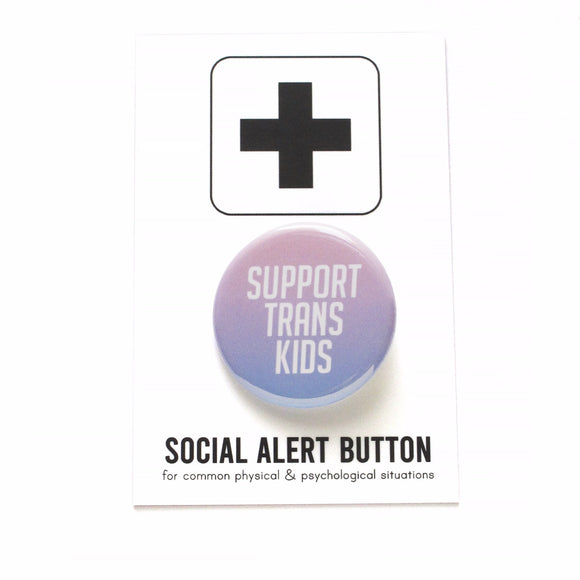 Round pinback button that says SUPPORT TRANS KIDS. Button is an ombre gradient of light pink to light blue  with white san serif text. The button is on a black and white Social Alert Button backing card with a black plus sign at the top.