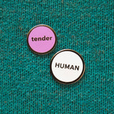 Round enamel pin that says TENDER next to a slightly larger white enamel pin that says HUMAN.  They are on a teal knitted background.