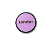 Round enamel pin that says TENDER. Silver text and outline with a lavender enamel background.