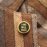 Round enamel pin that says TIME WILL PASS on the lapel of a brown striped tweed blazer.