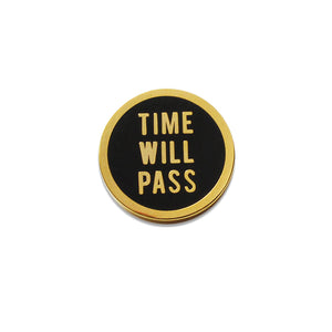 Round enamel pin that says TIME WILL PASS. Gold text and outline on a black background.