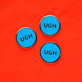 Three round, neon blue pins that say UGH, on a bright red fabric background.