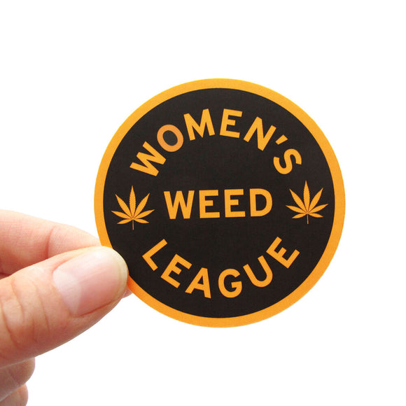 Round sticker that says WOMEN'S WEED LEAGUE.  Yellow-gold outline and font color, on a black background.  There are two pot leaves on each side of the word WEED.