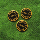 Three round WOMEN'S WEED LEAGUE enamel pins on a green textile background.