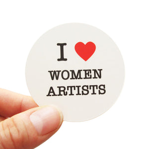 Round die-cut sticker that says I LOVE WOMEN ARTISTS. The text is black with a red heart signifies the word love. The background is white.