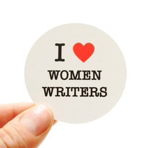 Round die-cut sticker that says I LOVE WOMEN WRITERS. The text is black with a red heart signifies the word love.  The background is white.