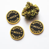 Three round WOMEN'S WEED LEAGUE enamel pins next to a nugget of cannabis
