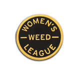 Round enamel pin that says WOMEN'S WEED LEAGUE. Gold text and outline on a black enamel background.