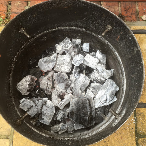 Spread the lit coals evenly in the bottom of the smoker